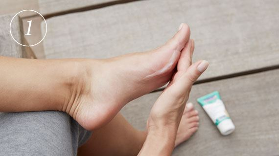 Woman applies Hansaplast ANTI CALLUS 20% UREA Intensive Cream on naked feet