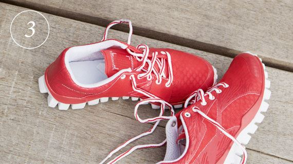 Red sport shoes laying on wooden ground